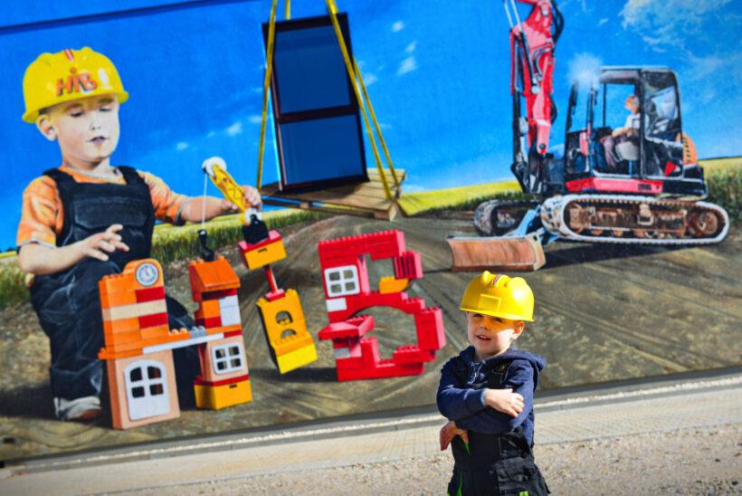 Junger Baumeister ziert betagte Fassade
